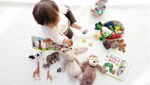 A toddler surrounded by toys.