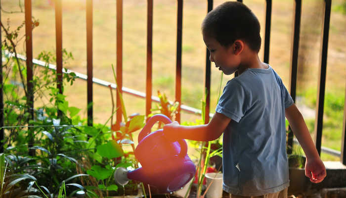 A child with a watering can. Image courtesy of Pixabay.com.