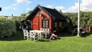 A garden playhouse with a child's tricycle. Image courtesy of https://cdn.pixabay.com/