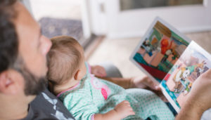 A dad reading a baby a story in the home, Photo by Picsea on Unsplash.