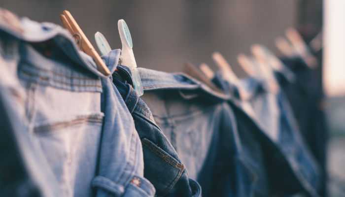 Jeans on a washing line. Photo by Bruno Nascimento on Unsplash.